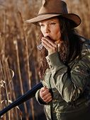 foto of shotgun  - Waterfowl hunting the female hunter carry a shotgun and she use a duck call shore and reeds on background - JPG