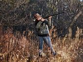 picture of shotgun  - Waterfowl hunting the female hunter use the shotgun autumnal bushes on background - JPG