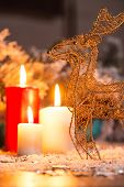 image of deer family  - Christmas decoration   like wicker iron deer at red and white lightning candles  and fir branches  with selective focus - JPG