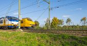 stock photo of high-speed train  - Passenger trains passing at high speed in sunlight - JPG