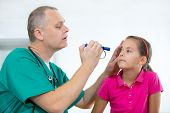 stock photo of ophthalmology  - Eye doctor examining young girl patient  - JPG