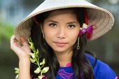 foto of conic  - Attractive serious young Vietnamese woman in a conical straw hat with a fresh flower in her hair looking at the camera with her hand to the brim - JPG