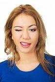 stock photo of blinking  - Beautiful happy woman blinks her eye - JPG