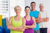 stock photo of arms race  - Portrait of confident fit people standing arms crossed at gym - JPG