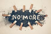 stock photo of ashes  - cigarette ash with text saying no more - JPG