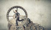 stock photo of hamster  - Young businessman in suit running in hamster wheel - JPG