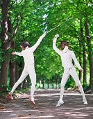 foto of rapier  - Two rapier fencer women fighting over park alley - JPG
