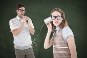 picture of tin man  - Geeky hipster couple speaking with tin can phone against green chalkboard - JPG