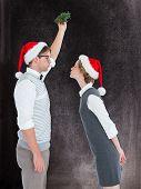 stock photo of mistletoe  - Geeky hipster kissing under mistletoe against black background - JPG