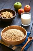 pic of oats  - Raw rolled oats in wooden bowl with fruits glass of milk and a bowl of fruit crumble in the back photographed on dark wood with natural light  - JPG