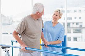 stock photo of therapist  - Senior man walking with therapist help in fitness studio - JPG