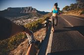 picture of pov  - POV shot of man stretching his leg with woman exercising by a road guardrail - JPG