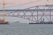 stock photo of bridges  - Construction of the new Forth Road Bridge taken from the south shore with the original road bridge and the rail bridge in the background - JPG