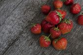 stock photo of crude  - several red ripe strawberries lying on a crude wooden surface - JPG