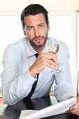 foto of sparkling wine  - handsome man drinking a glass of sparkling wine white sitting at the bar with newspaper - JPG