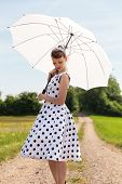 picture of fifties  - vintage fifties look with petticoat dress hairband und sunshade in the nature - JPG