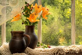 stock photo of asiatic lily  - Asiatic Hybrids orange lilies bouquet on a window sill in a sunny rainy day - JPG
