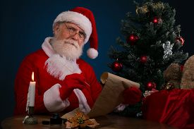 stock photo of letters to santa claus  - Santa Claus sitting near Christmas tree and writing a wish list - JPG