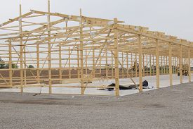 pic of lumber  - Lumber Frame for Storage Unit building under construction with lumber in place on concrete pad - JPG