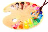 stock photo of paint brush  - wooden art palette with blobs of paint and a brush on white background - JPG