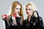 stock photo of domina  - women in latex with handcuffs and whip - JPG