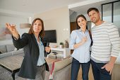 Couple with real-estate agent visiting house for sale poster
