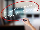Постер, плакат: Woman Hand Writing We Travel Not To Escape Life But For Life Not To Escape Us With A Marker Over T
