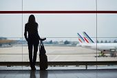Young Woman In The Airport, Looking Through The Window At Planes poster