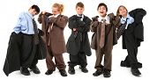 Adorable 7 year old children, boys and girls, in brown and blue baggy men's suits and big shoes over