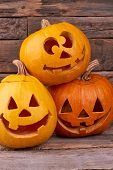 Three Funny Halloween Pumpkins. Funny Jack O Lntern Halloween Pumpkins On Wooden Background. Hallowe poster