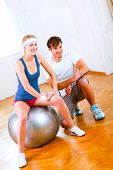 Portrait Of Sitting On Fitness Ball Slim Girl And Her Personal Trainer
