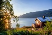 Norwegian wooden summer house (Hytte) with terrace overlooking scenic lake at sunset, Telemark, Norw poster