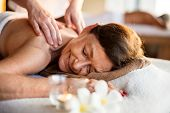 Female message therapist giving a massage at a spa poster