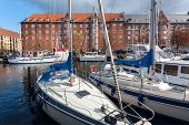 Sunny Day In Calm Bay With Moored Yachts, Old Brick Houses And Blue Sky Over Copenhagen, Denmark. poster