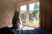 Young Woman Sitting On Bed And Enjoying View From Window. Peaceful Morning poster