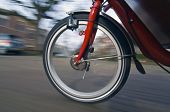 picture of dynamo  - The spinning and vibrating wheel of a delivery bicycle on a suburban street - JPG