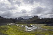 The green river bedding amongst the volcanic mountain ridges in the Landmannalaugar region Iceland on an overcast day poster