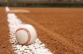 stock photo of infield  - Baseball on the Infield Chalk Line with Third Base beyond - JPG