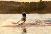 Wake Board A Man Does A Trick At Sunset On The Board On The Water Splashes poster