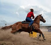 picture of barrel racing  - Cowgirl Rounding a Drum in the Barrel Race - JPG