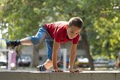 stock photo of parkour  - Young boy doing parkour exercise jumping over wall