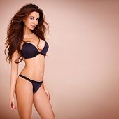 foto of curvaceous  - Sexy pose of a dark haired woman wearing a black bikini - JPG