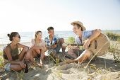 stock photo of spring break  - group of young people having fun on the beach - JPG