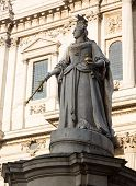 stock photo of sceptre  - Statue of Queen Anne with bird perched on crown in St Pauls Cathedral in London England at dusk as the sun is setting low in sky - JPG