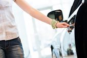 stock photo of showrooms  - woman opens the door to a new car - JPG
