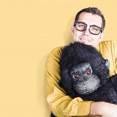 stock photo of gorilla  - Big goofy man cuddling soft toy gorilla on yellow background - JPG