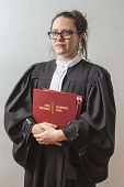 image of toga  - thirty something brunette woman wearing a canadian lawyer toga holding a red bilingual criminal law book - JPG