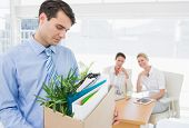 stock photo of forlorn  - Young businessman leaving office with his belongings and colleagues in background - JPG