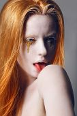 Fantasy. Expression. Eccentric Woman With White Painted Skin And Gold Tears Licking Her Shoulder