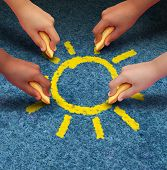 image of child development  - Community education and children learning and development concept with a group of hands representing ethnic groups of young people holding chalk cooperating together to draw a yellow sun shape as a metaphore for friendship - JPG